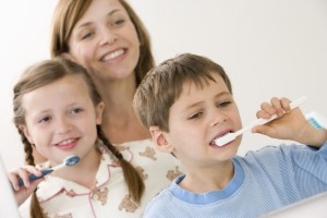 Mother watching children brushing teeth
